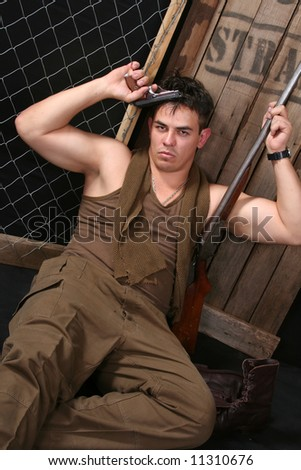 Sad emotional young soldier with weapons in studio - stock photo