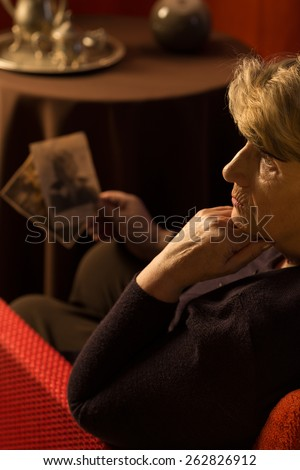 Sad female pensioner holding old family pictures - stock photo