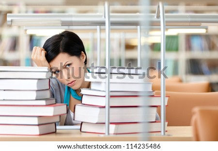 Sad female student is tired of learning surrounded with piles of books sitting at the desk - stock photo