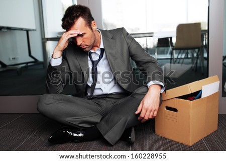 Sad fired businessman sitting outside meeting room after being dismissed