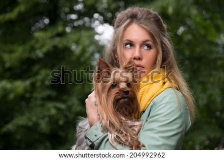 sad frightened blonde young woman with dog in the park - stock photo