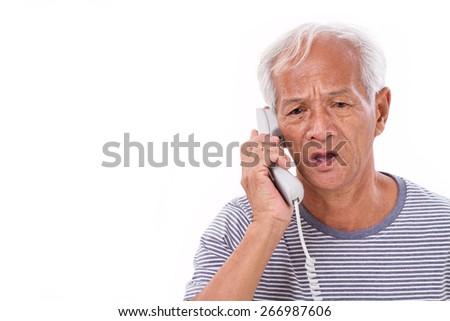 sad, frustrated, negative senior old man talking via home telephone - stock photo