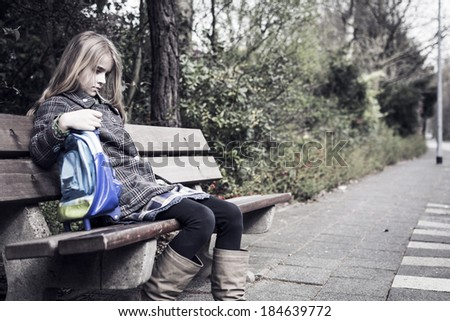 Sad girl after school, sitting on bench - stock photo