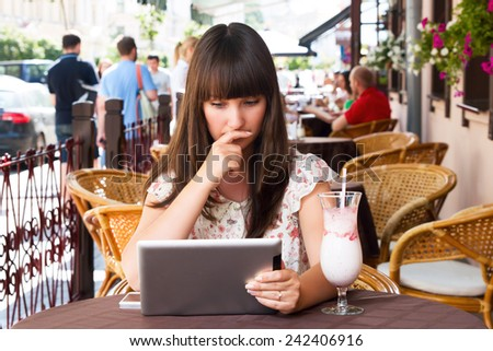Sad girl in a cafe looking into a tablet - stock photo
