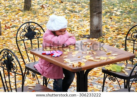 sad girl in the autumn. little girl sitting alone at a table cafe. girl in a pink coat was left alone. No family, no parents. Girl waiting for mum and dad. without family - stock photo