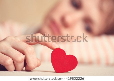 Sad girl is holding heart symbol by her finger and looking at it. Love and relationships concept - stock photo