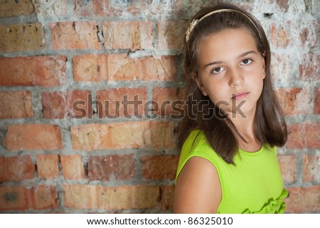 Sad girl is standing in front of a brick wall