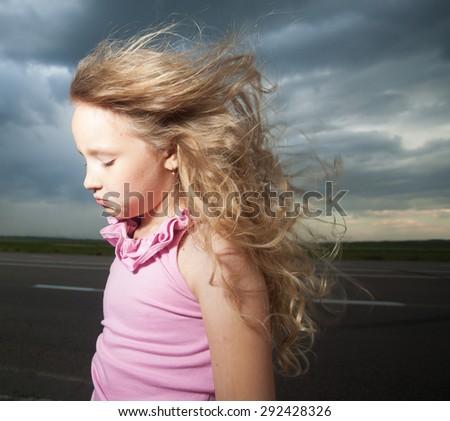 Sad girl near road. Child outdoors - stock photo