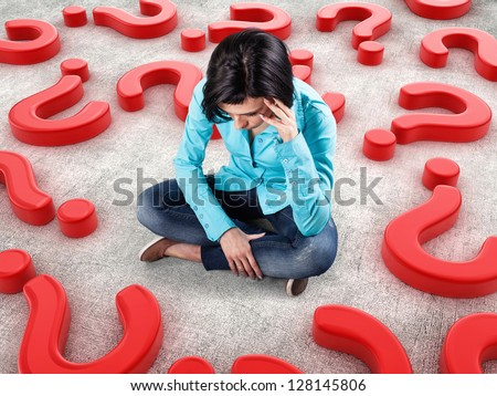Sad girl sits among many red questions - stock photo