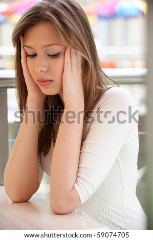 Sad girl sits at little table and looks downwards. - stock photo