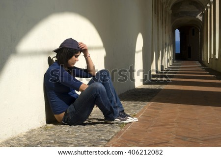 Sad girl sitting against wall
