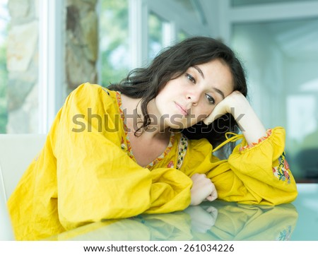 Sad girl sitting along at the table indoor - stock photo