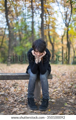 Sad girl sitting on a bench - stock photo
