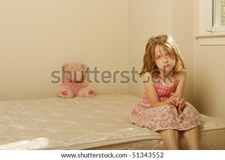 Sad girl sitting on old mattress - stock photo