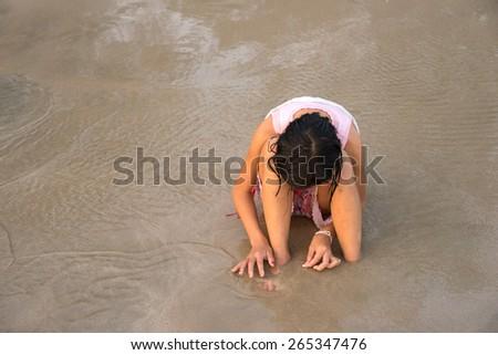 Sad girl sitting on sand at a beach. - stock photo