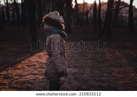 Sad girl standing in the park in autumn - stock photo