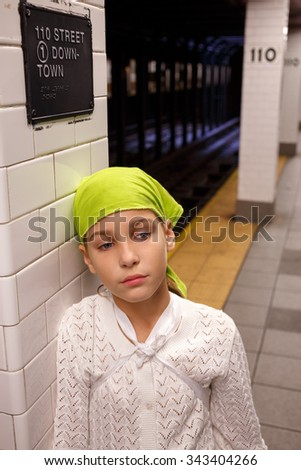 sad girl stands leaning against a column in the New York subway - stock photo
