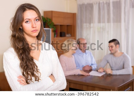 Sad girl staying against united family members - stock photo