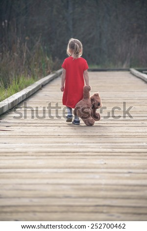 Sad girl walking on wooden path with teddy bear, view from behind - stock photo