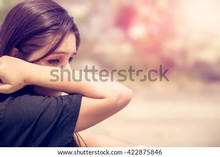 Sad girl wiping tears outdoors.  - stock photo