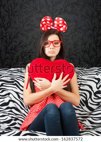 Sad girl with a big hair bow and a heart cushion sitting on the sofa and looking at camera - stock photo