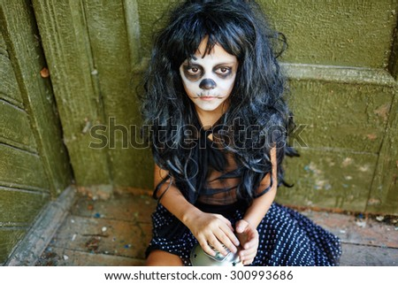 Sad girl with artificial hair sitting by wall of haunted house - stock photo