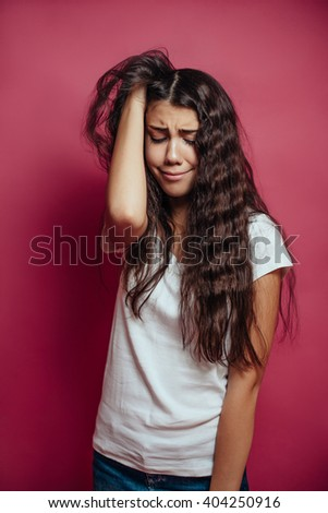Sad girl with long brunette hair on red background - stock photo