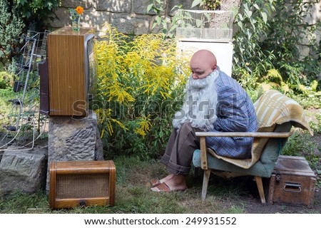 sad grandfather sitting outside with TV - stock photo