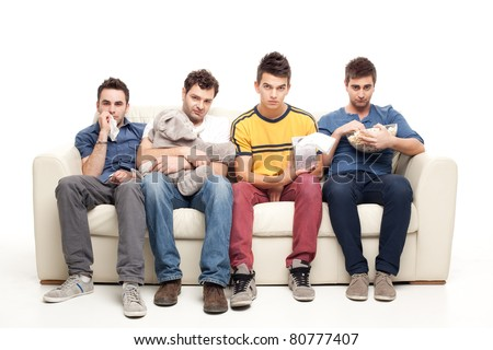 sad  group of young men looking at television sitting on a couch - stock photo