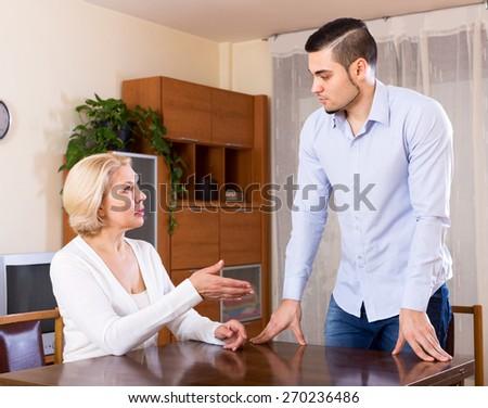 Sad guy and his mature girlfriend having serious conversation indoors - stock photo