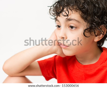 Sad Hispanic boy looking away. White background and a lonely boy who looks dishearted and bored. Worried little child with curly hair and wearing a red T-Shirt. - stock photo