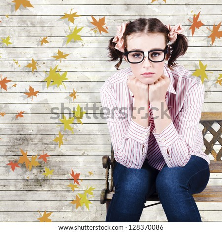 Sad Introvert Businesswoman Sulking In A State Of Depression While Sitting On An Autumn Park Bench Outdoors In A Depiction Of A Business Networking Crisis - stock photo