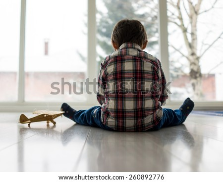 Sad kid sitting on floor - stock photo
