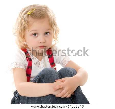 Sad little blond girl in red suspenders sitting on white background - stock photo