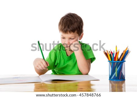 Sad little boy at the table with painting, isolated on white