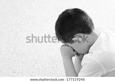 sad little boy crying with his head in his hands - stock photo