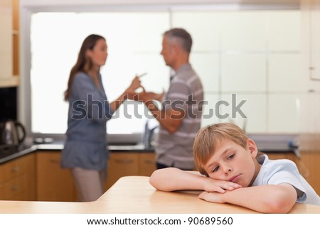 Sad little boy hearing his parents arguing in a kitchen - stock photo