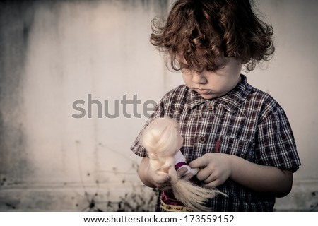 sad little boy hugging a doll - stock photo
