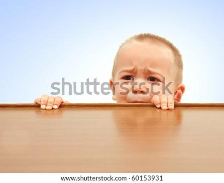 Sad little boy looking through table surface - stock photo