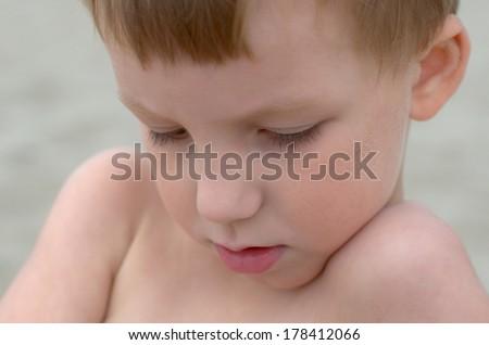 sad little boy on a sand beach - stock photo