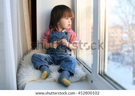 Sad little boy sits on sill and looks out of window in wintertime - stock photo