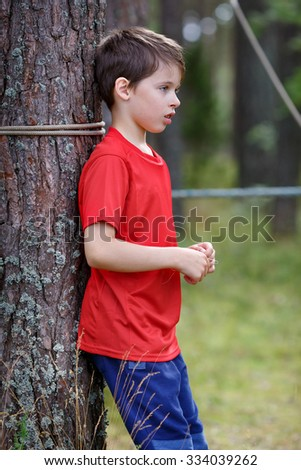 Sad little boy standing under the tree in forest - stock photo