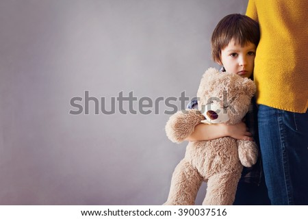 Sad little child, boy, hugging his mother at home, isolated image, copy space. Family concept - stock photo