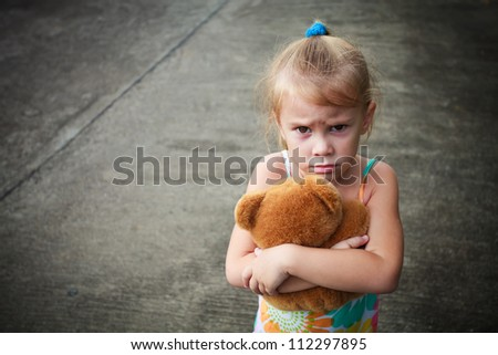 sad little girl holding toy with her hands