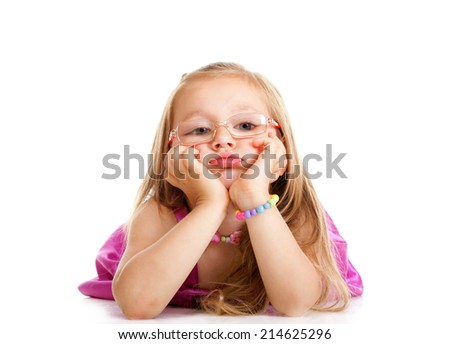 Sad little girl in glasses laying on floor leaning on elbows, chin in hands, looking isolated over white - stock photo