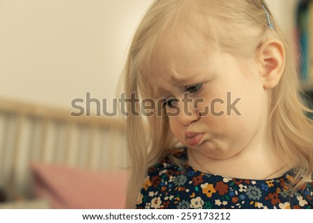 Sad little girl in her room. Looking down. - stock photo