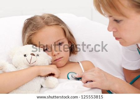 Sad little girl laying sick in bed checked by a doctor