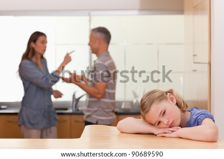 Sad little girl listening her parents having an argument in a kitchen - stock photo