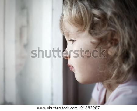 Sad little girl looking at window - stock photo