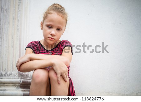 sad little girl on background the wall - stock photo
